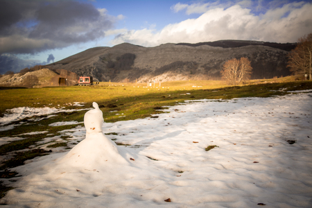 Horizontal View of a Snowman that is Melting during a Hot Day in Spring on Blur Mountain Landscape Background