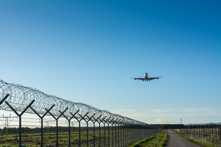 Horizontal View of a Cargo Airplane in the Landing Operation in the Morning on Blue Sky Background. Grottaglie, Taranto, South of Italy