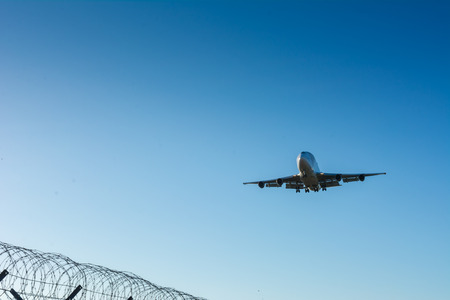Horizontal View of a Cargo Airplane in the Landing Operation in The Morning on Blue Sky Background. Grottaglie, Taranto, South of Italy Stock fotó