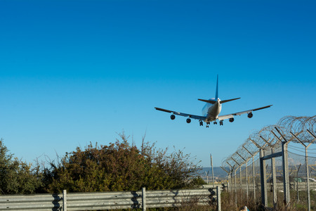 Horizontal View of a Cargo Airplane in the Landing Operation in The Morning on Blue Sky Background. Grottaglie, Taranto, South of Italy Stock Photo