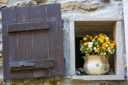 Horizontal View of a Little Open Window With a Flowered Pot in Riomaggiore. Italy, National Park of the Cinque Terre Stock Photo