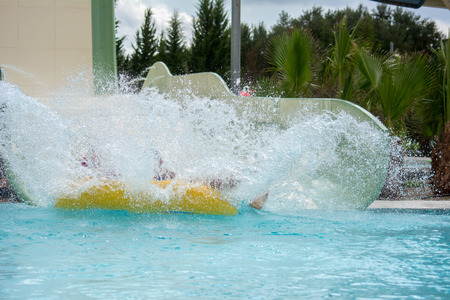 Inflatable Bot Splashing in the Swimming Pool at the Water Park in Summer on Blur Background
