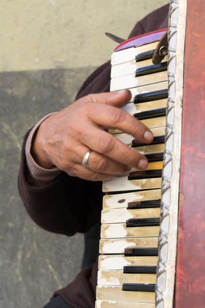 Close Up of Old Beggar Woman Playng a Dirty Accordion in the Street on Blur Background
