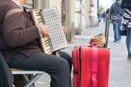 Close Up of Old Beggar Woman Playng a Dirty Accordion in the Street near a Red Suitcase on Blur Background