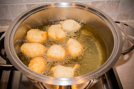 Dough Friying in a Pot during the Preparation of an Italian Christmas Traditional Dish called Pettole on Blur Background