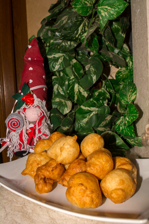 Close up of a Traditional Christmas Italian Food Called Pettole on Blur Cristmas Decorations Background Stock Photo