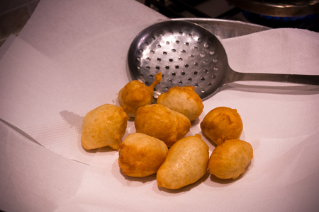 Italian Christmas Traditional Dish called Pettole just Fried on a Paper Towel on Blur Background