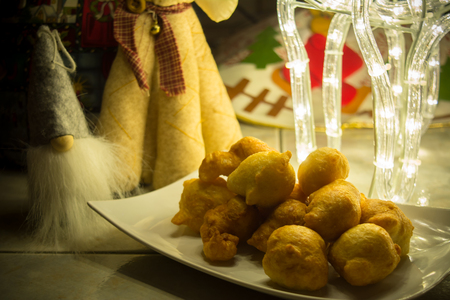 Close up of a Traditional Christmas Italian Food Called Pettole on Blur Cristmas Lighting Decorations Background
