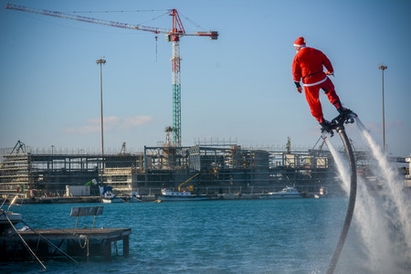 Horizontal View of Santa Claus on Flyboard on Blur Background. Taranto, Italy