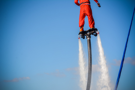 Horizontal View of Santa Claus on Flyboard on Blue Sky Background. Taranto, Italy Stock Photo