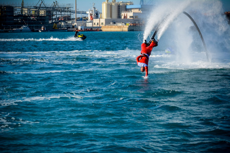 Horizontal View of Santa Claus Diving in the Sea on Flyboard on Blur Background. Taranto, Italy