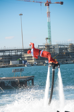 Vertical View of Santa Claus Flying on Flyboard on Blur Background. Taranto, Italy Stock Photo