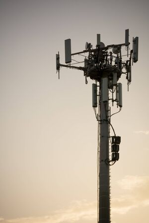 Close Up of Cellphone Tower at Sunset on Partially Cloudy Background