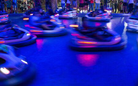 Cerca de coches chocadores borrosa corriendo en la noche en un Luna Park en el sur de Italia sobre fondo borroso Foto de archivo