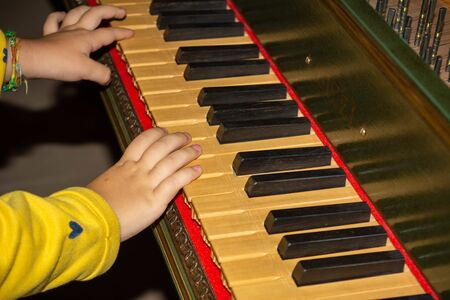 Hand of Child Playing Medieval Harpsichord in a Castle in Italy on Blurred Background