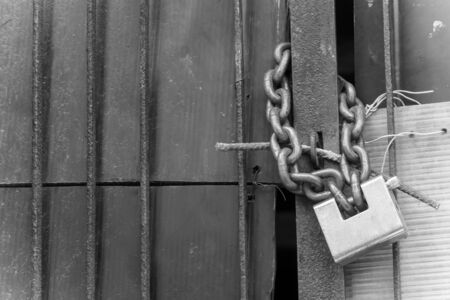 Padlock and a Chain on old Gate on Blurred Background