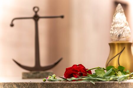 Anchor and a Red Rose on a Tomb in Italian Cemetery on Blurred Background Reklamní fotografie