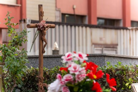 Christian Statue in the Day of Commemoration of the Dead in Italian Cemetery on Blurred Background