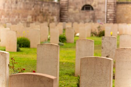 Tombs in a Field in the Day of Commemoration of the Dead in Italian Cemetery on Blurred Background