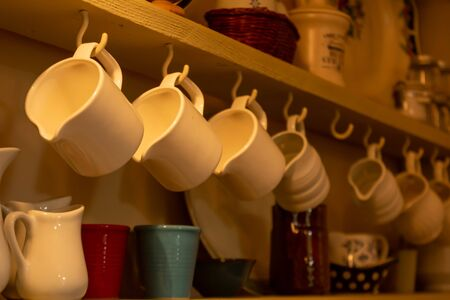 Close Up of Tea Cups Hanged on the Cupboard in English Cottage in Countryside  on Blurred Background Reklamní fotografie
