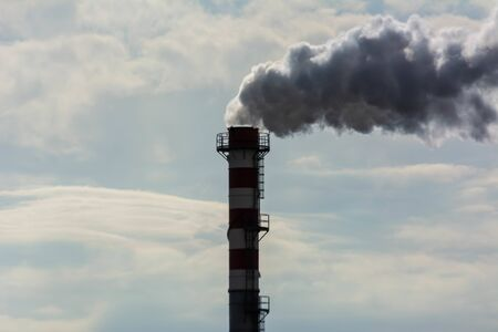 Red and White Chimney Smoking on Cloudy Sky Background. Pollution in the Atmosphere