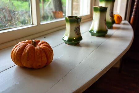 Close Up of Pumpkin and Pots in English Cottage in Countryside in front of Window on Blurred Background