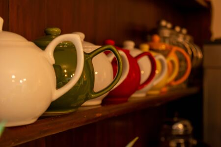 Close Up of colored  Teapots in English Cottage in Countryside  on Blurred Background