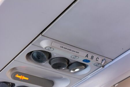 Close Up of Air Flows and Safety Belt Signage on the Airplane on Blurred Background
