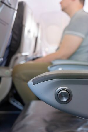 Close Up of Armrest inside an Airplane during Flight on Blurred Background
