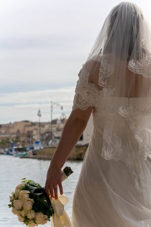 Bride Holding Brides Bouquet in front of the Sea on Blurred Taranto Vecchia Bluildings Background in Italy. Abandoned Bride 版權商用圖片