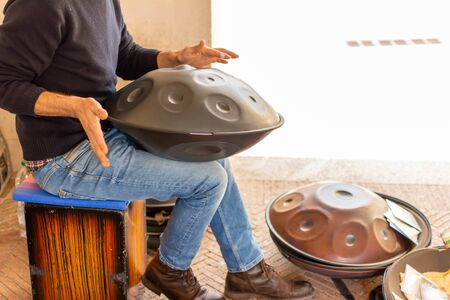 Musician Playing Handpan on Blurred Background in Matera, South of Italy