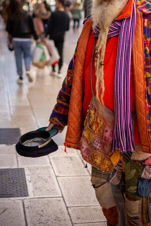 Old Man in Colorful Clothes asking for Alms on the street during Christmas Period in Taranto, South of Italy