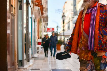 Old Man in Colorful Clothes asking for Alms on the street during Christmas Period in Taranto, South of Italy 版權商用圖片 - 136015832
