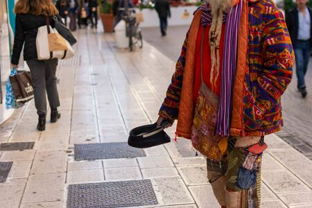 Old Man in Colorful Clothes asking for Alms on the street during Christmas Period in Taranto, South of Italy 版權商用圖片 - 136015888