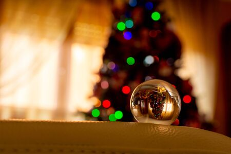 Christmas Tree Shape reflected in a Glass Sphere on Blurred Background 版權商用圖片 - 136015604