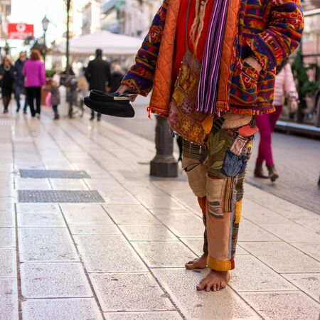 Old Man in Colorful Clothes asking for Alms on the street during Christmas Period in Taranto, South of Italy 版權商用圖片 - 136015615