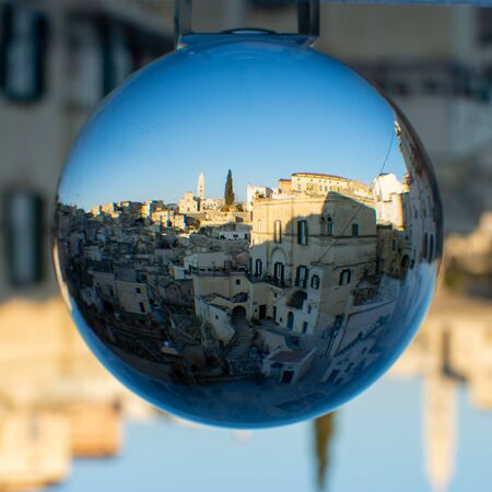 The Sassi di Matera enclose d in a Cristal Sphere on Blue Sky Background