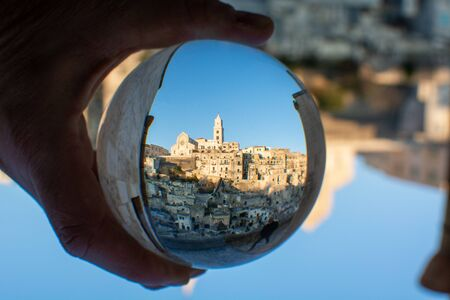 The Cathedral of Matera in Ialy in the Middle of the Sassi di Matera enlosed in a Cristal Sphere Holded by a Hand on Blue Sky Background