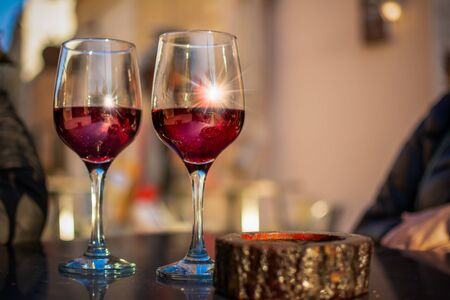 Close Up of a Pair of Red Wine Glasses on a Table on Blurre Background