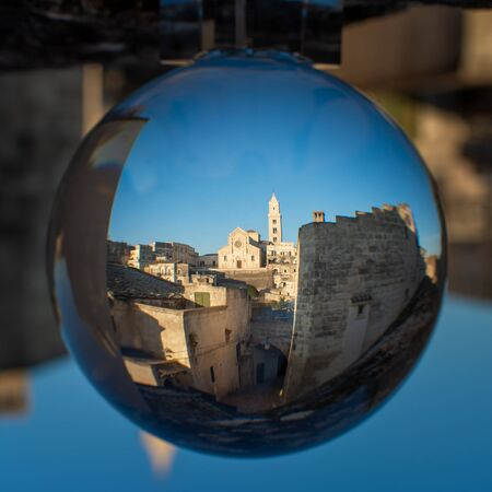 The Cathedral of Matera in Ialy in the Middle of the Sassi di Matera enlosed in a Cristal Sphere on Blue Sky Background 版權商用圖片 - 137732927