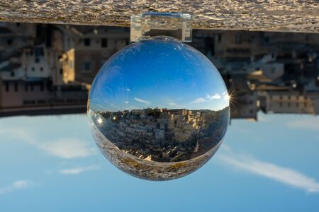 The Sassi of Matera enclosed in a Cristal Sphere on blue Sky Background 版權商用圖片 - 137732885