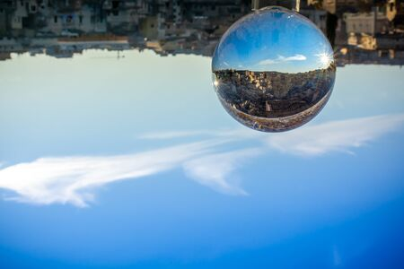 The Sassi of Matera enclosed in a Cristal Sphere on blue Sky Background