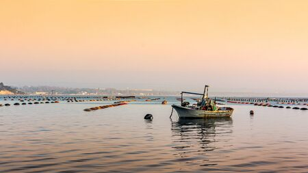 Small Boat Moored in Vicinity of Mussil Plantation In Italy. Mar Piccolo VIew at Sunset in Taranto, Italy