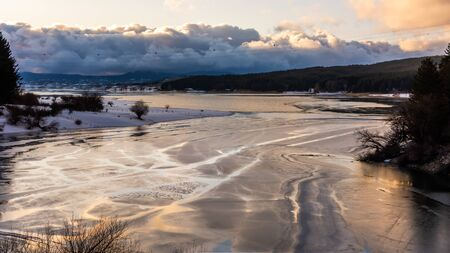 Panoramic View of Cecita Lake in Winter, partially covered by Ice. Iced Lake in Italy. Winter in Italy.Iced Lake at Sunset 版權商用圖片