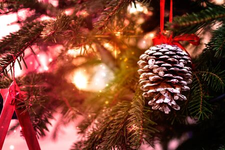 Close Up of Colored Pine Cone in Christmas Atmosphere. Blurred Lights Christmas 版權商用圖片