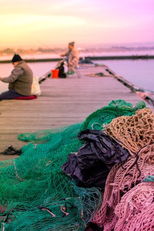 Close up of Waste Abandoned on a Berth and a Blurred Old Fisherman that Fishes. Taranto, Italy. Mar Piccolo at Sunset. Romantic and Relaxing View