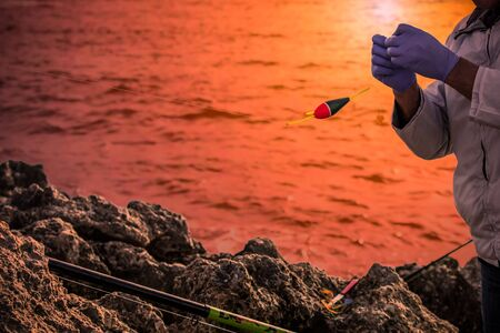Fisherman that prepares the bait for fishing on Blurres orange Background. Relaxing Moment in front of the sea 版權商用圖片