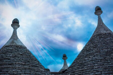 Panoramic view of ancient traditional  buildings called Trulli in Alberobello. Sunset between the Trulli in Italy on Blurred background