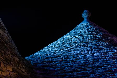 Panoramic view of the City of Alberobello with ancient traditional Italian Bluildings called Trulli on blurred backgound. Alerobello at night illuminated by colored lights