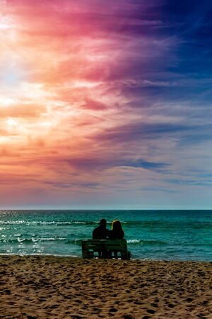 Romantic couple on the beach at colorful sunset on harts background. Perfect tropical sunset landscape, exotic nature view. Happy romantic couple enjoying beautiful sunset at the beach. Saint Valentine s Day celebration 版權商用圖片